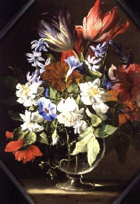 A Vase of Flowers on a Stone Ledge Containing Tulips, Chrysanthemums, Dahlias and Narcissi