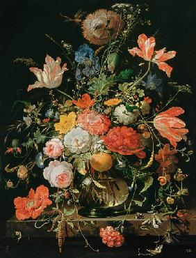 A glass with flowers and orange branch