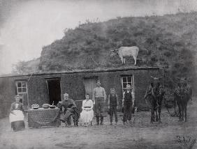 American pioneer family in front of their home (b/w photo)