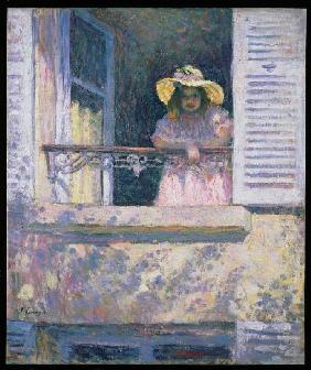 Young girl with sunhat at the window