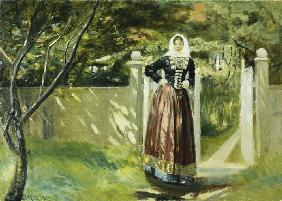 Woman in Danish dress at the garden gate