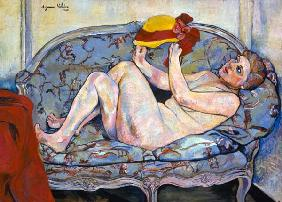 Lying female act on a chaise longue with hat in the hand.